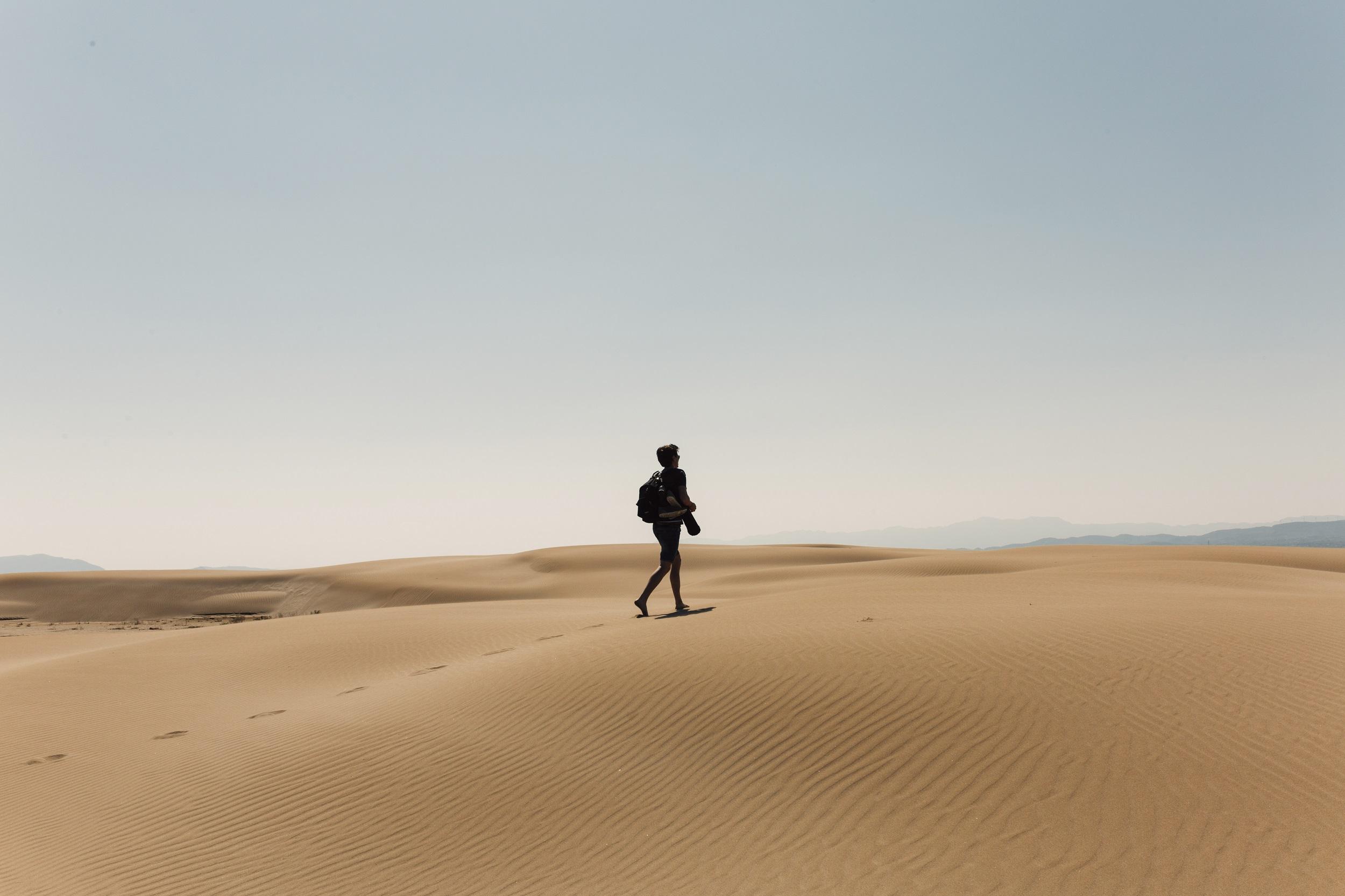 Full Length Of Hiker With Backpack Exploring Desert Against Sky