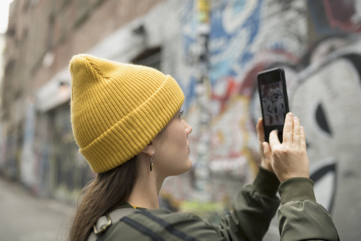 Young Woman With Camera Phone Photographing Graffiti On Urban Wall