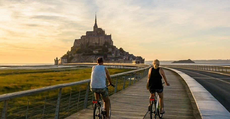 http://View%20Of%20The%20Mont%20Saint%20Michel%20Tidal%20Island%20In%20Normandy,%20France,%20At%20Sunset%20With%20A%20Couple%20Biking%20To%20The%20Town%20On%20The%20Wooden%20Jetty.