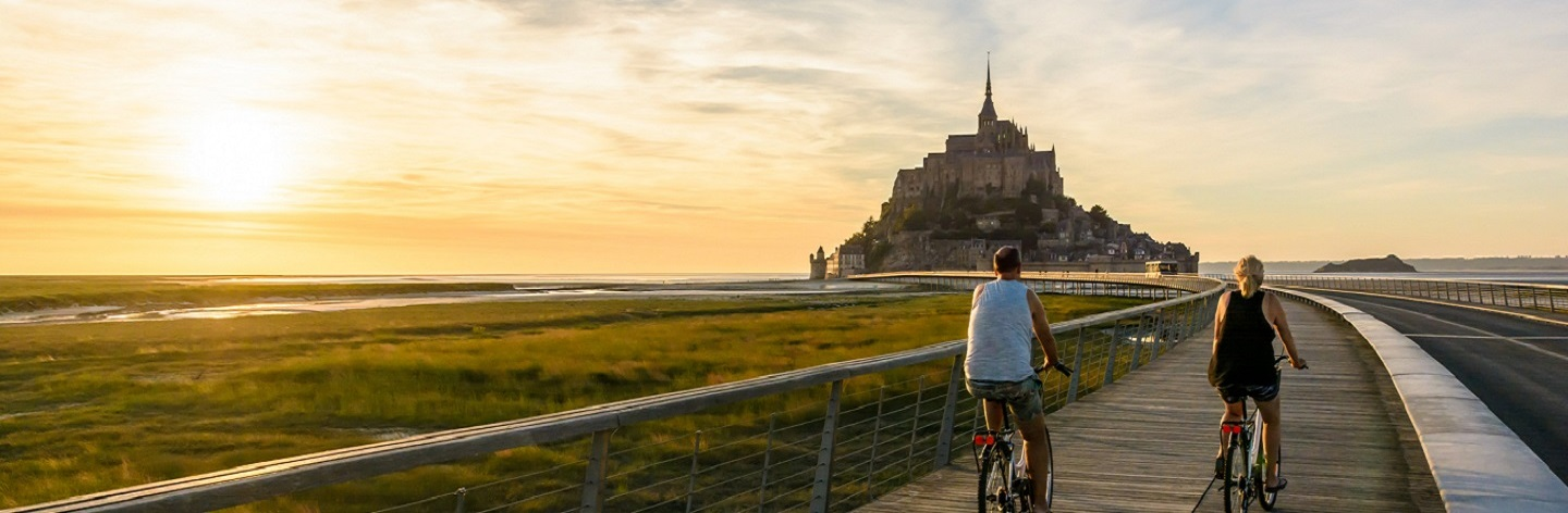 View Of The Mont Saint Michel Tidal Island In Normandy, France, At Sunset With A Couple Biking To The Town On The Wooden Jetty.