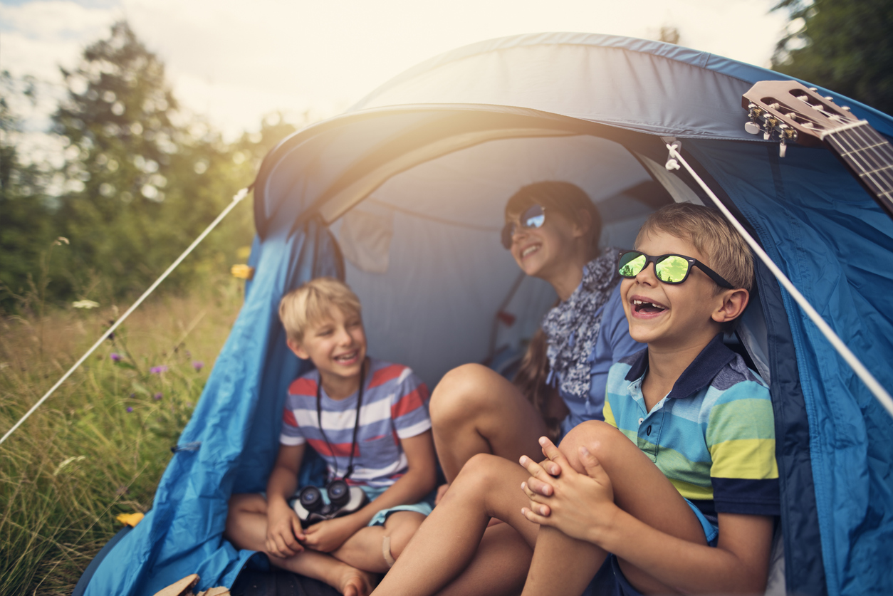 Kids Having Fun Camping In Tent On The Forest Meadow